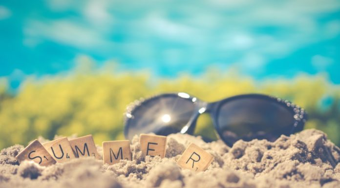 Summer spelled out in scrabble letters with sunglasses in the background. Inexpensive summer ideas