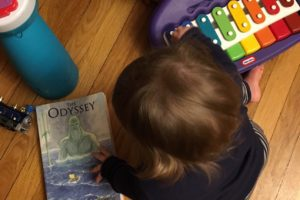 toddler girl with book and toys Providence Moms Blog