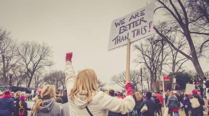 woman and crowd protesting gun violence and wanting gun control Providence Moms Blog