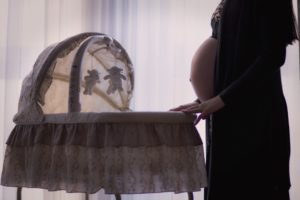 pregnant woman standing by bassinet Providence Moms Blog