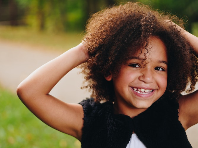 young girl with curly hair smiling Providence Moms Blog