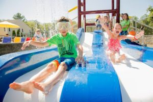 Boy in goggles and bathing suit and girl in bathing suit with arms raised up on a a waterslide at the splash pad a the Bernon Family YMCA. Providence Moms Blog Guide to splash pads in MA and RI