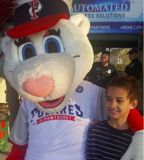 kid at Paw Sox game with mascot Providence Moms Blog