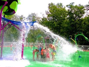 Group of children ducking as water splashes down on them from a giant structure in a splash pad. Splashpads featured in Providence Moms Blog guide to RI, MA and beyond
