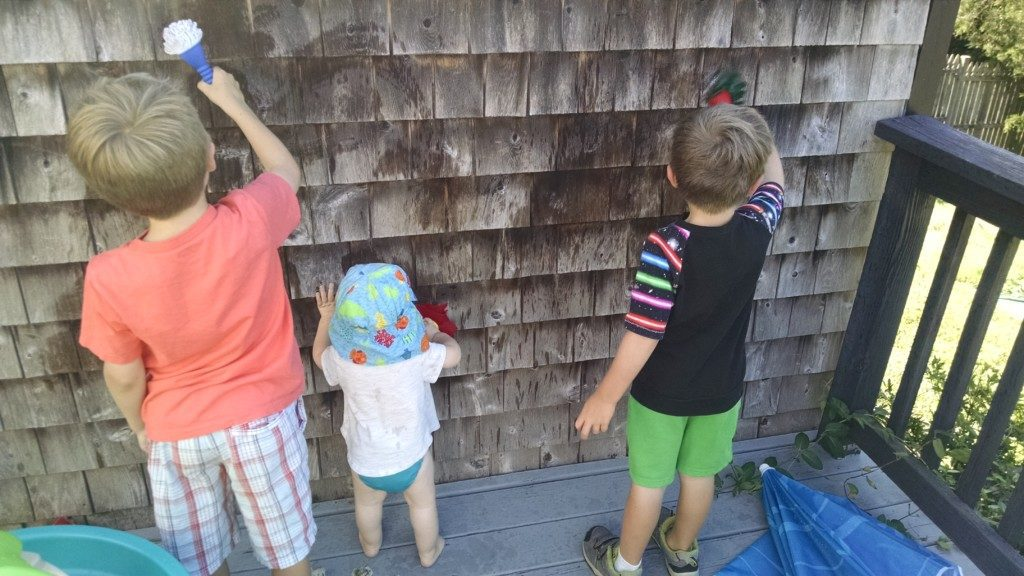 three children painting with water on exterior of house Providence Moms Blog