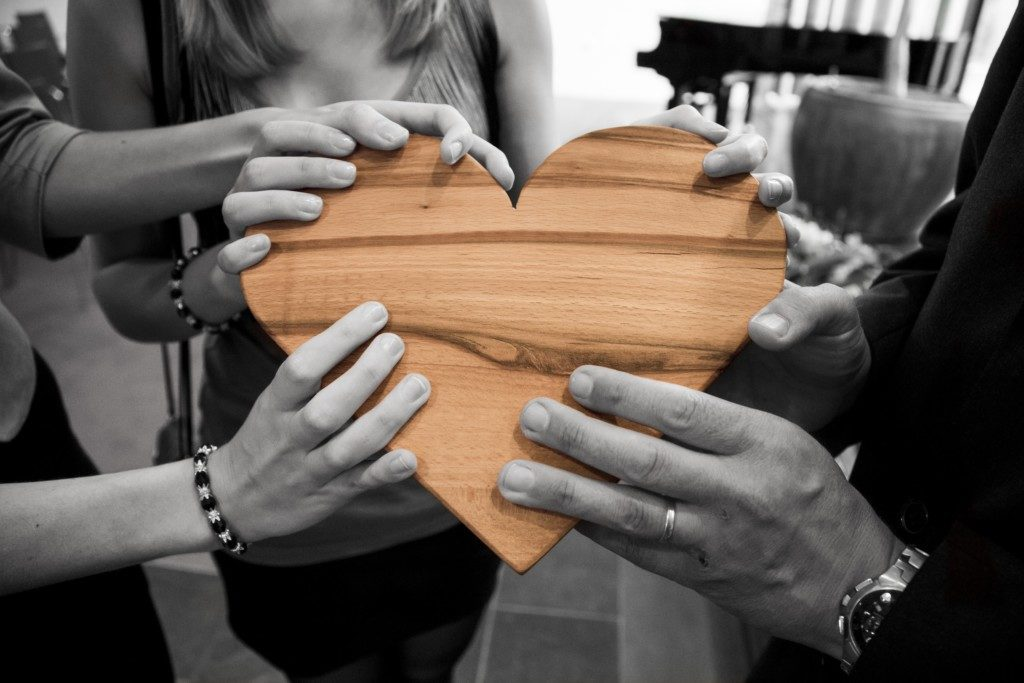 group of adults holding a wooden heart Providence Moms Blog