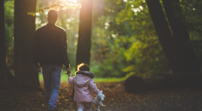 Father walking with daughter in woods Providence Moms Blog