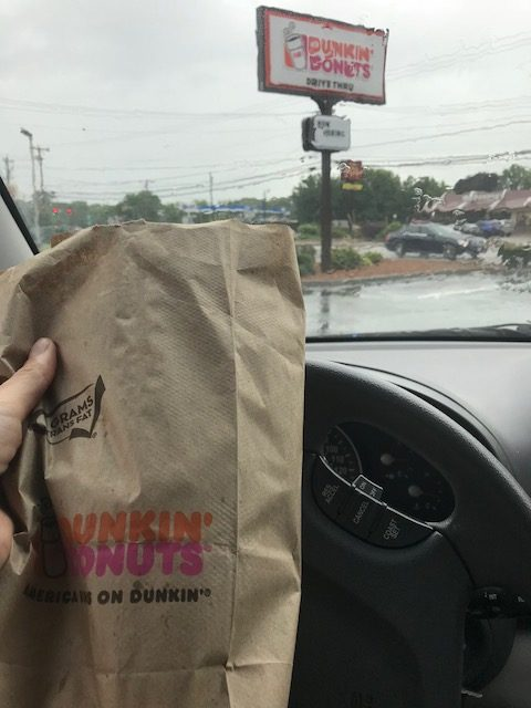 Dunkin' Donuts bag shot from the inside of a car with a Dunkin Donuts sign in the background. Author is on a Dunkin' Run.