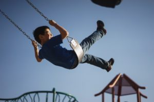 boy swinging on swing Providence Moms Blog