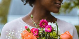 woman holding cup of flowers Providence Moms Blog