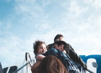 Family boarding airplane from stairs Providence Moms Blog