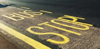 bus stop written on street in yellow paint