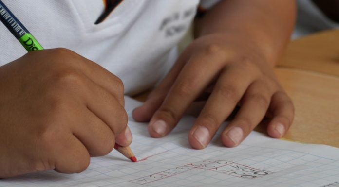 Childs hands holding a colored pencil completing school work as part of Providence Moms Blog post about RICAS
