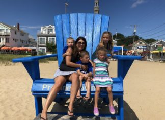 photo of mom and 4 children in giant chair at beach