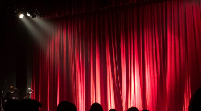 Theater with red curtain and spotlight. Several shadowed heads of audience members visible. Part of Providence Moms Blog post on budget friendly activities