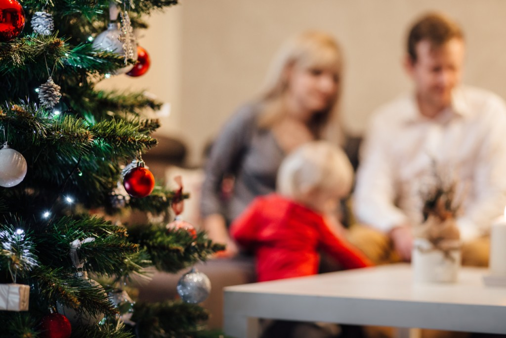 Decorated Christmas Tree with blurry blond headed small child and two adults in the background. Picture in Providence Moms Blog Post on Holiday Stress