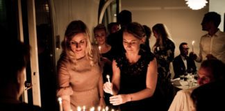 Two women standing by a birthday cake with lit candles. Image in Providence Moms Blog post on life lessons