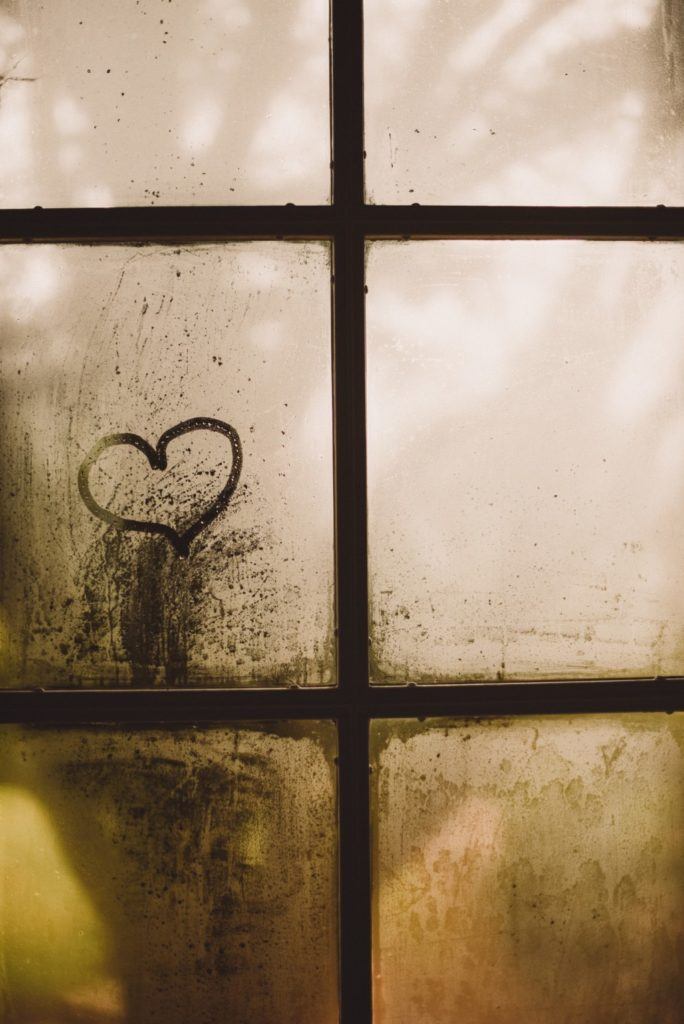 Dirty windowpane with heart shape sketched onto it. Providence Moms Blog article on children's feelings.