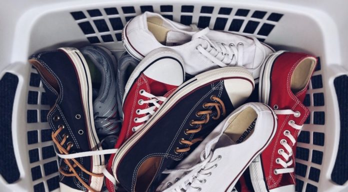 Many pairs of shoes in a laundry basket. Decluttering failure article.