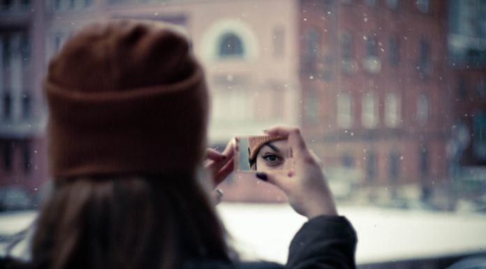 Photo of woman looking at the reflection of her eye in a small mirror with a building and snow in the background. Providence Moms Blog post on self care.