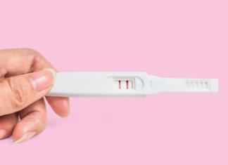 hand holding a positive pregnancy test stick, fertility