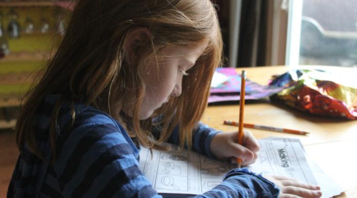 girl sitting at able doing homework