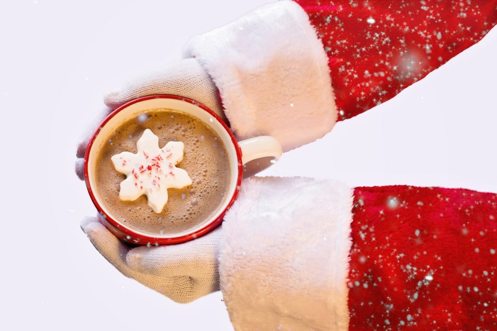 santa hands holding mug of hot chocolate with snowflake inside