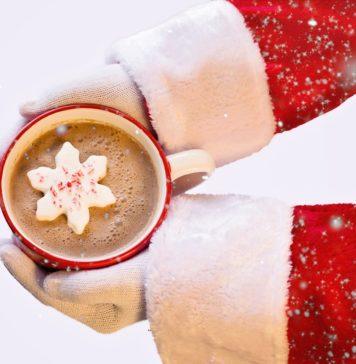 santa hands holding mug of hot chocolate with snowflake inside
