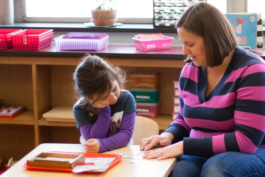 teacher and student working at Ocean State Montessori School