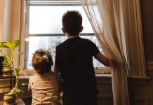 2 children looking out window