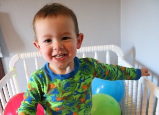 toddler in crib with birthday balloons