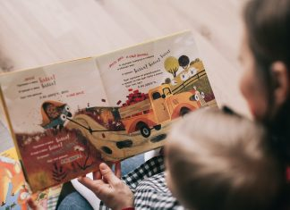 daycare teacher reading book to toddler