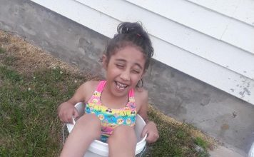 brown child smiling wearing bathing suit in bucket
