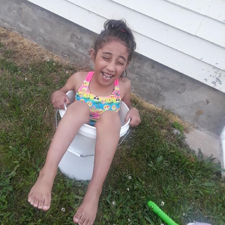 brown child smiling wearing bathing suit in bucket