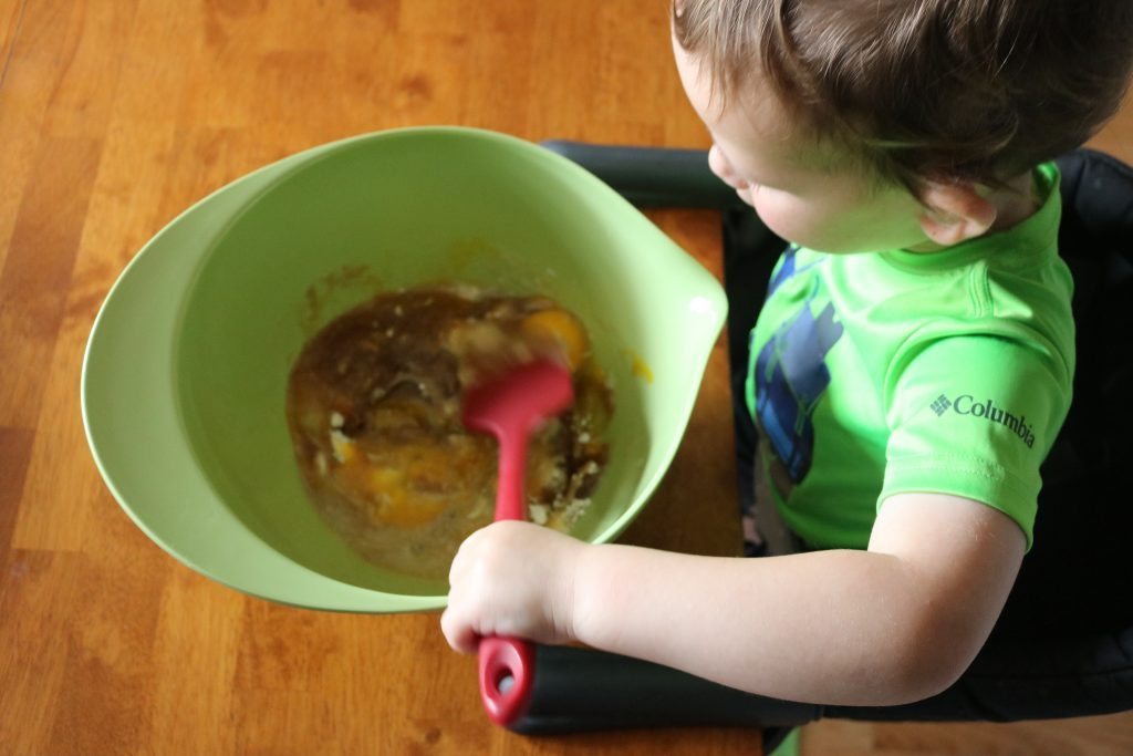 A small child helps mix pie filling