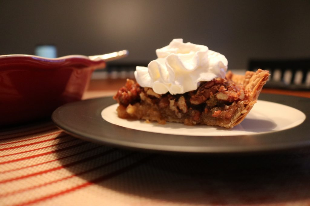 A slice of pecan pie served with whipped cream