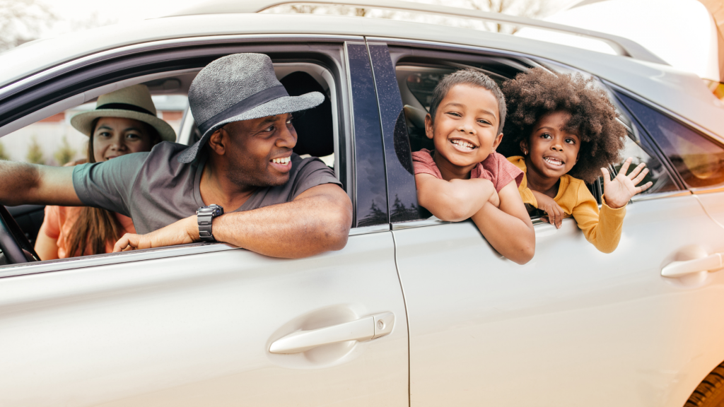 black man, woman, two children smiling in vehicle mini vacation   Providence Mom