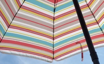 young white boy at the beach under colorful umbrella